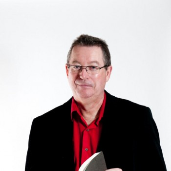 Eric Walters smiles while holding a book