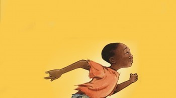 A young African boy runs smiling to school. All but two fingers on his hands are malformed