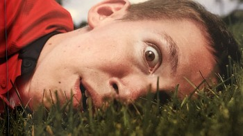 Shane Burcaw, the author of Not So Different, lies sideways in deep grass. His facial expression is one of surprise